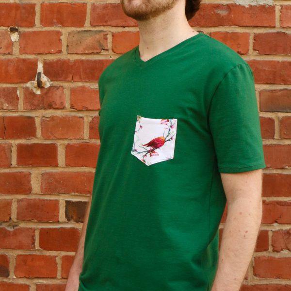 mann mit gruenem shirt mit Brusttasche auf der ein Vogel abgebildet ist von fraenne