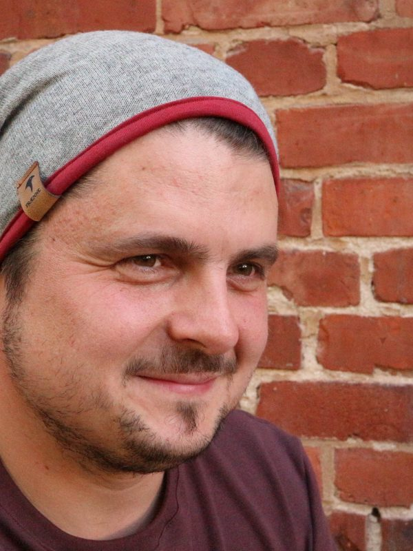 mann mit beanie mütze in grau und rot von fraenne