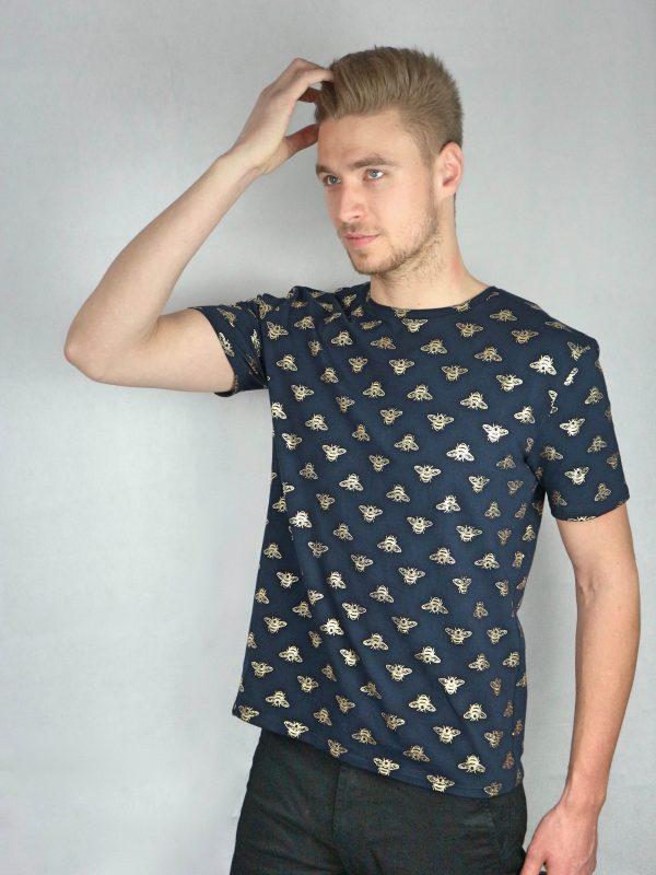 mann mit dunkelblauen t-shirt mit goldenen bienenaufdruck von fraenne